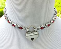 PLEASE READ THE ITEM DESCRIPTION COMPLETEY....  My chainmaille collars are handmade by me, one ring at a time.  Weave: Byzantine  Chain: Jewelry grade anodized aluminum jump rings. Available in bright silver with your choice of accent ring color (RED is shown). This petite square chain measures 1/4 thick.  Clasp: small heart shaped NICKEL padlock with two keys, 1 1/8 x 3/4.  SIZING: Take a LOOSE measurement, preferably with a seamstress tape, around the BASE of the neck. ADD AT LEAST ONE…
