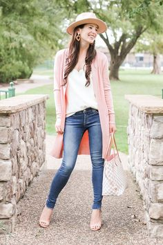 Casual fall outfit idea-- Amazon long pink cardigan styled with a white J.Crew Factory scalloped cami top, AG super skinny jeans, Louis Vuitton Neverfull Damier Azure dupe bag, Amazon nude block heel sandals, and Amazon Lanzom wool wide brim fedora. Click through for affordable fall outfit details from popular affordable style blogger Stephanie Ziajka on Diary of a Debutante! #falloutfit #amazonfashion #fallfashion #affordablefashion #fallstyle #fallootd #louisvuitton #dupebags