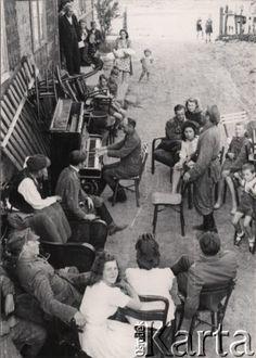 1945-1946, Polska.  Ziemie Odzyskane, osadnicy wojskowi - byli żołnierze Dywizji Kościuszkowskiej razem z rodzinami, z lewej siedzi mężczyzna grający na pianinie.  Fot. Tadeusz Olszewski, zbiory Ośrodka KARTA, udostępniła Anna Olszewska