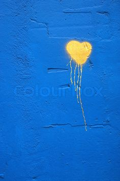 Stock image of 'painted yellow heart sign on blue wall'