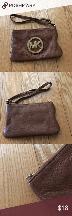 Michael Kors Brown Wristlet Leather Michael Kors Wristlet with two inside pockets. Very durable leather with signs of ware. The pull is missing from the zipper and a few stains on the inside. The emblem has some tarnish and scratches. However the wallet has plenty of life left. Michael Kors Bags Clutches & Wristlets