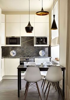 Cucine bianche dal design moderno, ante di colore bianco con paraschizzi in marmo e lampade a sospensione