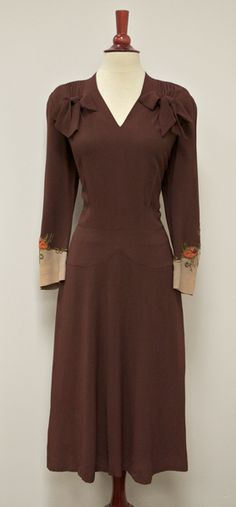 Dress: ca. 1940's, beaded crepe, embellished with bows and pleating, sleeves end with applique, beading and embroidery.