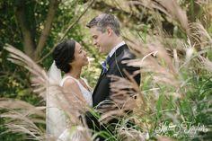 Bride and groom hug in the tall grasses. James Gardens, Toronto wedding photography.