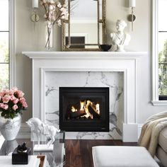 designed by The Design Company. Lovely living room with a white fireplace mantel and beautiful styling #blackandwhiteinteriors