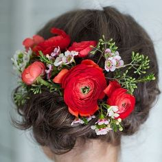 Ranunculus flowers in the hair add a soft and colorful touch