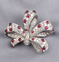 Platinum, Ruby, and Diamond Bow Brooch, Tiffany & Co., set with round cabochon rubies, further set with full-cut diamond melee, approx. total wt. 3.50 cts., lg. 1 1/2 in., signed.