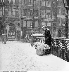 Bloemenverkoper tijdens sneeuwbui, Leidsestraat, Amsterdam (1940-1945) fotograaf: Charles Breijer