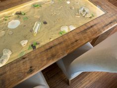 Build a rustic-chic dining table that features a glass-capped tabletop filled with sand, sea glass and your favorite seashells. From the experts at DIYNetwork.com.