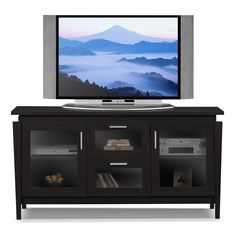 """Sleek Chic. If you love contemporary furnishings, you've found the perfect piece in the Duvall 60"""" TV stand. With simple yet refined lines in this stand's top, its tapered silhouette and sleek, silver-hued bar pulls, this television stand exudes modernity. Two central drawers display media components smartly and pull out for convenient access. The cabinets feature tempered-glass, framed fronts and a pedestal-style top, while the rich merlot finish fits well in most living spaces and color…"""