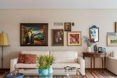 Decoração com personalidade, decoração colorida de sala de estar com obras de arte, almofada estampada, mesa lateral, tapete e sofá branco.