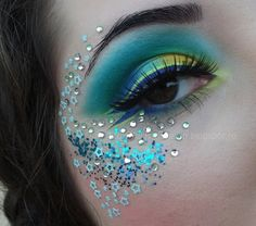 Crystals, glitter and stars accent beautiful yellow, green and blue eye shadow.