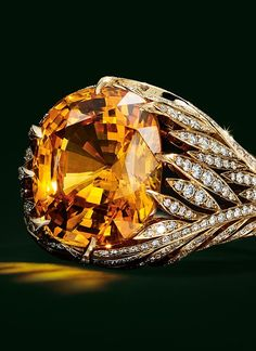 Ring in 18k gold with a cushion-cut orange sapphire of over 11 carats and diamonds.