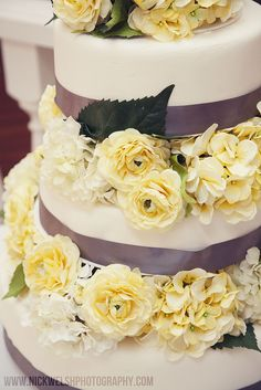 Beautiful wedding cake with brownish-purple ribbon and light yellow flowers. www.nickwelshphotography.com