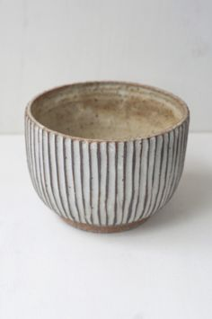 A deep bowl with a hand-carved line pattern, and a finish that reminds us of the patina on ancient vessels. A good size for bringing fruit salad to the table.Fr