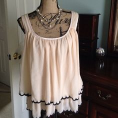 Peaches and cream top This is a beautiful top from H&M size 10. I love the peach colored tiered layers with black scalloped edges.  Its in perfect condition with absolutely no signs of wear.  No snags or stains.  This top would look amazing paired with black shorts or capri pants and a set pearls to complete your look. Open to reasonable offers H&M Tops Tank Tops