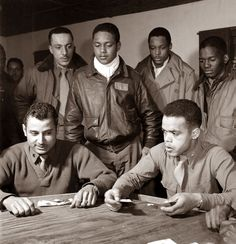 group of men playing cards. They are members of the famous Tuskegee Airmen. This was a special air force fighter wing in World War II made up of black men.
