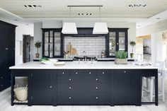 This standout modern country Neptune kitchen is finished in a bold charcoal which looks striking against a white backdrop.