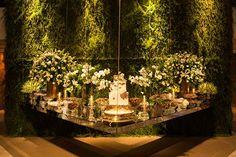 A mesa do bolo suspensa e em formato de L foi o destaque da decoração de casamento com muitas folhagens assinada pela 1-18 Project.