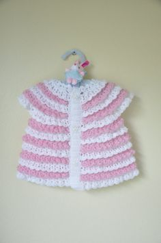 This is a hand knitted baby vest.  -Made out of 100% acrylic.  -Three white buttons with smiley stars.  -Fits from 8 months to 24 months.  -Length