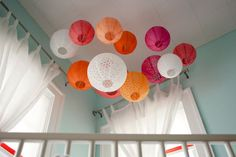 Wow. What a gorgeous alternative to a mobile. Paper lanterns in different colors strung above a crib.