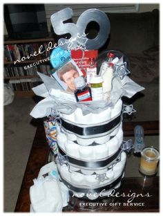 Custom 50th Birthday Adult Diaper Cake - Includes items like Geritol, Old Spice, Hair Dye, Pill Case, RX for Youth, etc... Novel Designs Executive Gift Service custom@noveldesignsllc.com