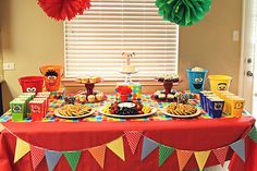 Really cute Sesame street party - pinning so I can remember some of her tricks and apply to Helens. Pom Poms, cupcake stands, wrapping paper as table runner, framed pics with polka dot paper