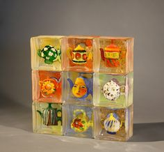 Stephanie Trenchard, NINE TEAPOTS, Sand Cast Glass with Sculpted and Painted Inclusions, 12 3/4 x 12 1/4 x 3""