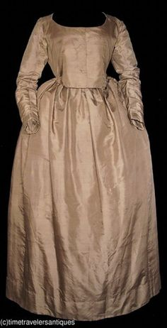 1775 lady's chestnut brown silk satin one piece day dress. A linen lined bodice with shoulder plackets and a deep 2 part V back construction, underarm triangular gussets to the long slender sleeves, two different calico printed cotton lining materials to the sleeves, a directionally pleated waistband with a closure at the side to the unlined skirt, and side slits below the waist to reach pockets that would be worn beneath the skirt. A pinked sarcenet faced hem.
