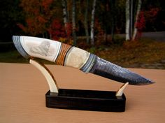 Knives by Ulf Brandt - My own blade made of Damascus, Blue, brown and white mammoth tusk, fossil walrus, pewter and spacer, my own scrimshaw. Stand: Ebony, mammoth tusk, gold plated silver. Best regards/ Ulf