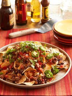 Classic Nachos~ Ingredients: 5   cupsbite-sized tortilla chips (6 ounces), 1 pound ground beef, 1   15 ounce can black beans or pinto beans rinsed and drained, 1   cup bottled chunky salsa, 1 1/2 - 2   cups shredded cheddar, Colby Jack, or Mexican cheese blend (6 ounces),   Optional toppings (such as thinly sliced green onion, snipped fresh cilantro, seeded and sliced fresh jalapeno chile pepper, sour cream, and/or additional bottled chunky salsa)