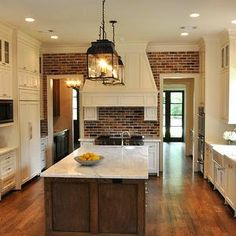 I love the farmhouse feel of this kitchen - clean and bright (white/cream cabinets and countertops) with the warm brick, stained island and dark metal light fixtures.
