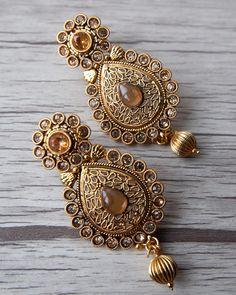 Antique gold earring with accent gold stones and matching  gold beads.  Visit us at www.aavarna.com  Like us on FB: Aavarna  #bridesmaid #indianwedding #wedding #jewelry #bollywood #indianfashion #shaadi #indianbride #hindubride #earrings #forsale #bollywoodfashion #indianfashion #jhumka #fashion #asianbride #onestopweddingshop #bridalwear #kundan #baju #traditional #stunning #instafashion #fashiontrend #aavarna #southindianfashion #tamil #tamilbride #hindubride #aavarnacollections #earrings…