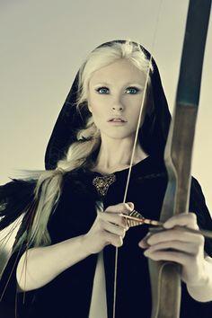 Lady archer in a dark blue cloak.