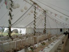 I love this.  I really like the greenery wrapping round the marquee poles, bunting (might want slightly stronger colours) the hessian table runner and little flower pots.