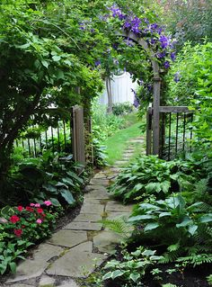 ...may have pinned this already!  Gorgeous flagstone garden path and arch with purple clematis