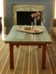 An old cabinet door, a piece of glass and an old coffee table create a new piece of furniture.