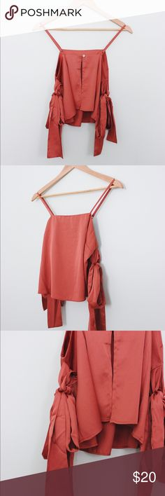 Satin rust tank top A rust orange color satin tank top with an open back and arm wraps. The arm wraps can be secured by tying a bow. A great addition to the closet! Tops Tank Tops