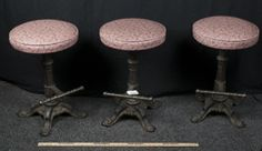NICE SET OF THREE MATCHING BAR OR DINING STOOLS WITH CAST IRON BASES AND BUILT IN FOOT REST BAR. THE STOOLS HAVE EASY TO CLEAN SOFT CUSHION TOPS. THE FEET HAVE SCROLLED SHELLS AND ORNATE RIBBON LIKE LINES. MEASURES 2 FEET HIGH AND 1 FOOT 4 INCHES WIDE. NICE STURDY STOOLS, BUYER TAKES ALL!