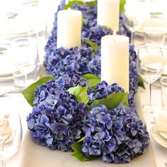 Gorgeous table runner of artificial deep blue hydrangeas from Amaranthine Blooms and white candles. Perfect for an elegant wedding centrepiece of the best quality silk flowers. www.amaranthineblooms.co.uk