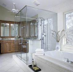 Larger and more luxurious, this new bath includes furniture-quality cabinetry and a jetted soaking tub. A glass-wall shower furthers the openness. Light-color tile enhances the traditional style of the bathroom while enabling sunlight to bounce around the space.