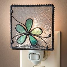 """J Devlin NTL 129-3 Stained Glass Aqua Blue Flower Night Light. Tiffany stained glass night light in aqua blue and clear vintage textured glass. Decorative beaded edging has been added to this night light. 4 watt bulb included. Handcrafted stained glass night light made with lead free solder to protect you and the environment. Designed and Manufactured by J Devlin 3"""" x 1 1/2"""" x 4 1/2""""."""