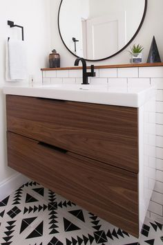 Geometric, black and white patterned floor tile injects a dash of whimsy and a lot of style into this bathroom. Flat panel wooden drawers neutralize the graphic floor and add warmth to the all-white space. Black fixtures give the vanity a contemporary look.