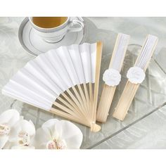 Elegant White Personalizable Paper Fan | Nuptial Knick Knacks  Keep your guests cool and comfortable with our white paper fans. Each fan is elegantly folded and is secured with a special thank you label. These fans are ideal for your outdoor or garden wedding ceremony and make unique wedding favors. They are the perfect addition to a springtime wedding or a beach ceremony.