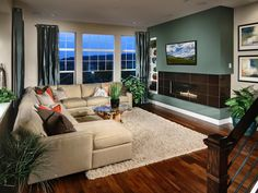 This neutral modern living room features a striking green focal wall with a tiled fireplace and flat screen TV.