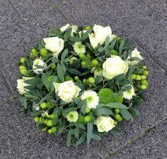 Krans met witte roosjes en sliert van groene hypericumbessen.