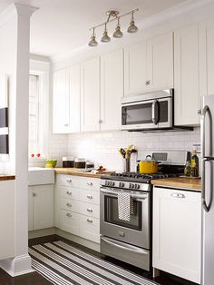 White cabinets, farmhouse sink, both IKEA finds, keep in step with this apartment's vintage origins, as do pulls and latches.