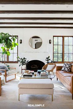 22 Chic and Clean Modern Living Room Design Ideas | In this minimal-Scandi style living room, by Homepolish designer Katherine Carter, less is more. While a statement piece is a must to liven up the space, it's important to keep things simple, like with this round mirror, or the space can become overwhelming. #realsimple #livingroomdecor #livingroomideas #details #homedecorinspo