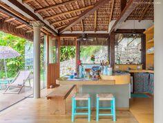 Cozinha de casa de praia tem armários e bancada da pia de alvenaria .