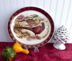 This is a vintage oval serving platter in a pattern of pheasants or game birds with a burgundy border with metallic gold overlay by Wood & Sons, England made between 1956 and 1962. The ironstone oval platter or serving platemeasures 9.5 inches high by 10.5 inches long and features a male and female pheasant. The platter is in very good +++ used vintage condition with no chips, cracks or wear and only mild age crazing. So decorative on a holiday or other dinner table or wall in any room…